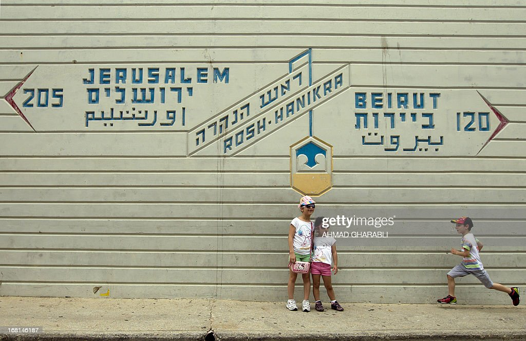 Children pose for a photograph under a sign indicating the direction and distance to the Lebanese capital Beirut and to Jerusalem at the Israel-Lebanon border crossing in Rosh Hanikra, on May 6, 2013.