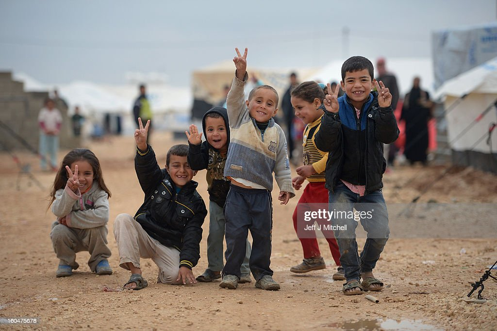 ZA'ATARI, JORDAN - FEBRUARY 01: Children pose for a picture as Syrian refugees go about their daily business in the Za'atari refugee camp on February 1, 2013 in Za'atari, Jordan. Record numbers of refugees are fleeing the violence and bombings in Syria to cross the borders to safety in northern Jordan and overwhelming the Za'atari camp. The Jordanian government are appealing for help with the influx of refugees as they struggle to cope with the sheer numbers arriving in the country.