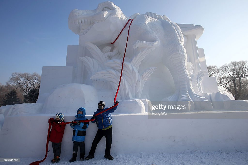 Children pose for photograph beside a large snow sculpture of dinosaur at the 26th Harbin International Snow Sculpture Art Expo in Sun Island park on December 22, 2013 in Harbin, China. The Harbin International Ice and Snow Sculpture Festival is one of the largest ice and snow festivals in the world and is a popular winter destination for both Chinese and foreign visitors.
