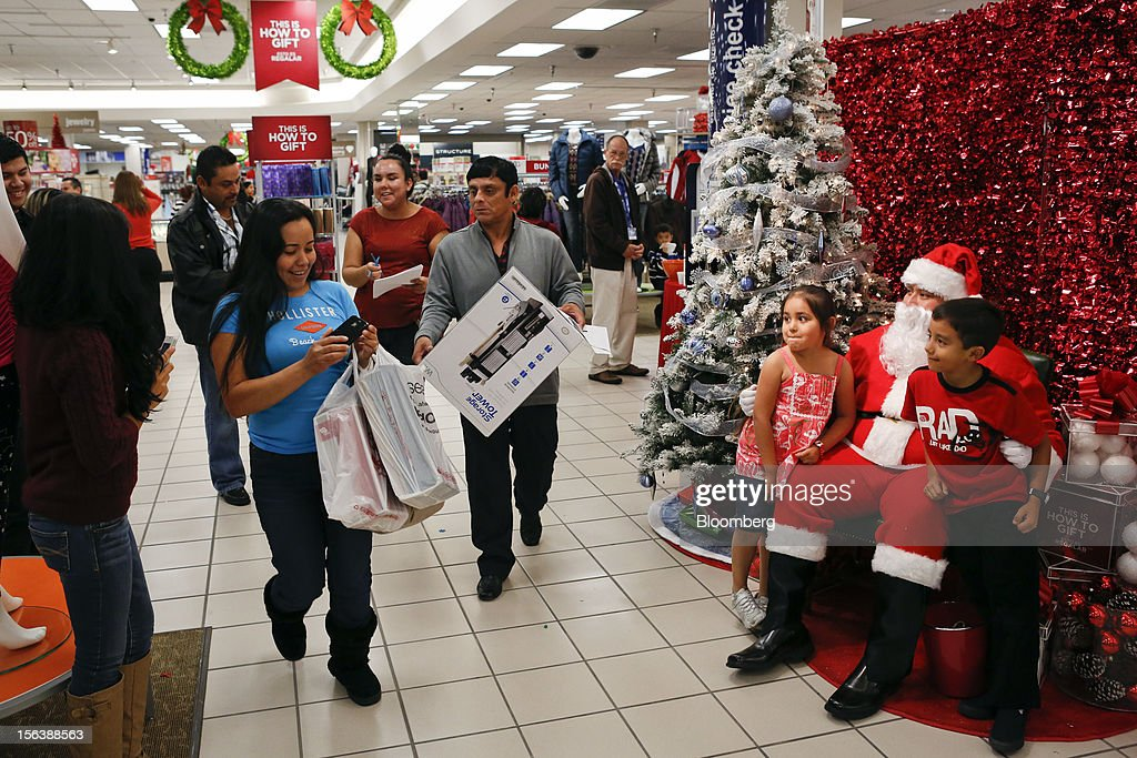 Children pose for pictures with Santa Claus at a Sears store during the Family and Friends evening sale inside the Del Amo shopping mall in Torrance, California, U.S., on Sunday, Nov. 11, 2012. Sears Holdings Corp. is scheduled to announce earnings results on Nov. 15 before the opening of U.S. financial markets. Photographer: Patrick Fallon/Bloomberg via Getty Images