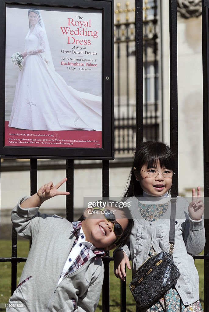 Children pose in front of a poster advertising the display of Kate Middleton's royal wedding dress, outside Buckingham Palace in central London as the palace opens its doors to the public for the summer on July 23, 2011, to showcase highlights including the dress worn by Kate Middleton when she married Prince William in April. It was the best kept secret of the royal wedding, but now the Alexander McQueen dress worn by the former Kate Middleton when she married Prince William is being put on public display for all to admire. Catherine's ivory and white satin-gazar dress, designed by Sarah Burton, goes on show at Buckingham Palace as part of the annual summer opening, where hundreds of thousands of visitors are expected to flock to see it.