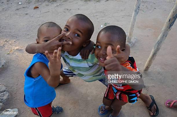 Children pose next to a football field in the Cidade de Deus shantytown in Rio de Janeiro Brazil on May 11 2013 AFP PHOTO/CHRISTOPHE SIMON