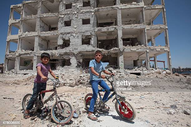 Children pose on their cycles in front of a destroyed building in the center of the Syrian town of Kobane also known as Ain alArab Syria June 20 2015...