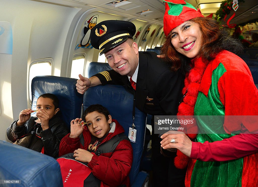 Children pose with a Delta pilot at the 3rd Annual Garden of Dreams Foundation & Delta Air Lines' 'Holiday in the Hangar' event at John F. Kennedy International Airport on December 11, 2012 in New York City.