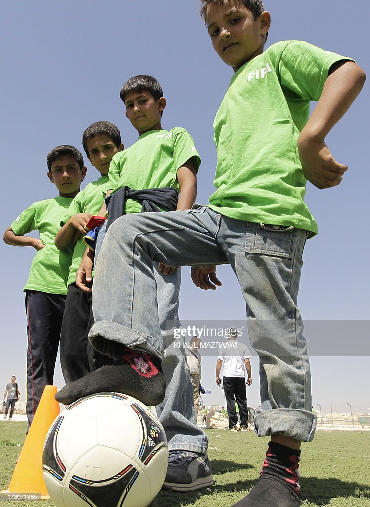 Children pose with a football ball at the northern Jordanian Zaatari refugee camp on July 6, 2013 in Mafraq near the border with Syria.