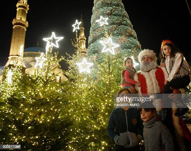 Children pose with a man dressed as Santa Claus in front of a giant Christmas tree designed by Lebanese fashion designer Elie Saab and displayed...