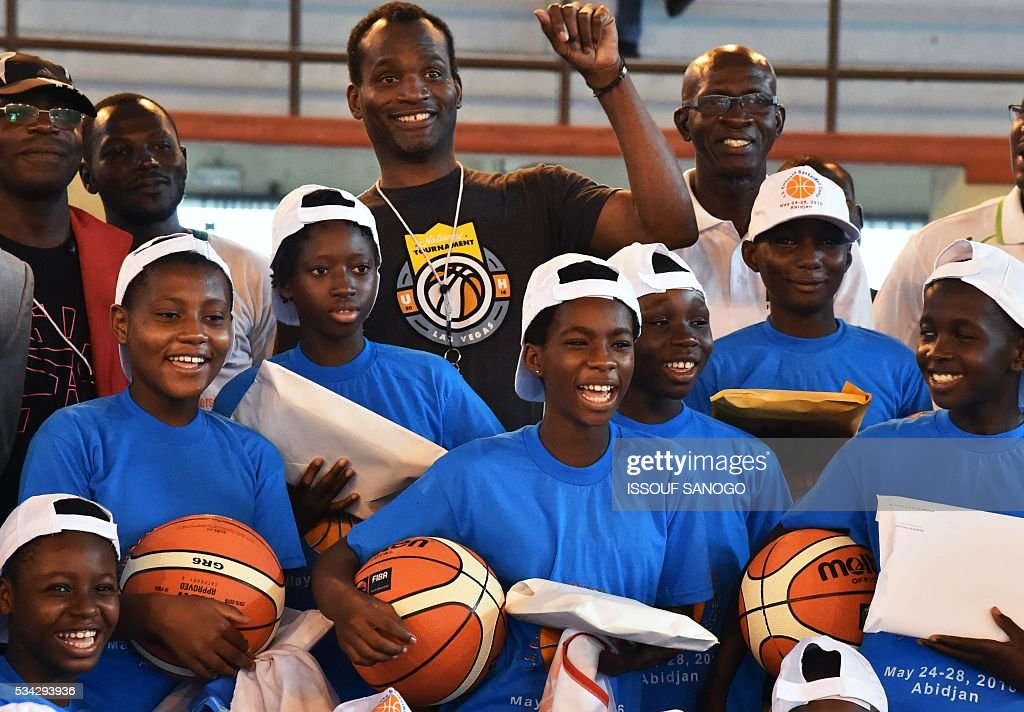 Children pose with American player Tommy Davis after a basketball match during the four days of workshop organised by the US embassy at the Felix Houphouet-Boigny University in Abidjan on May 25, 2016. / AFP / ISSOUF