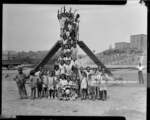 Children posing on sliding board ladder at playground on Kennard Field with Terrace Village housing project in background Pittsburgh Pennsylvania c...