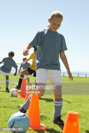 Children (9-12) practicing dribbling soccer ball : Stock Photo
