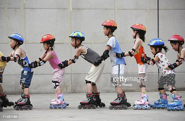Children practise roller skating at a street on July 12 2006 in Chongqing Municipality China Roller skating has become a compulsory physical...