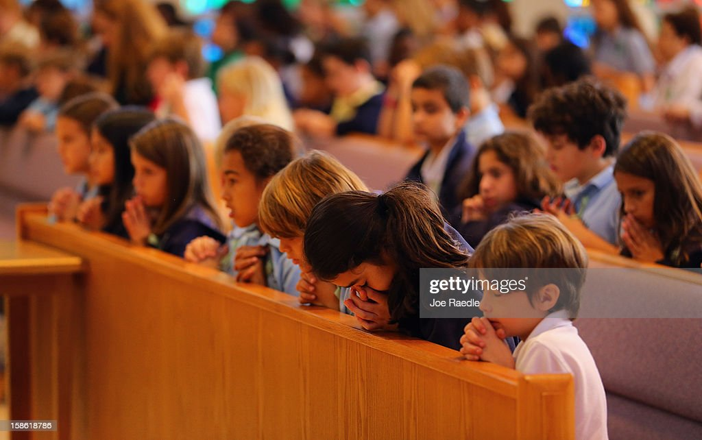 Children pray during a service, at St. Rose of Lima School, for the victims of the school shooting one week ago in Newtown, Connecticut on December 21, 2012 in Miami, Florida. Across the country people marked the one week point since the shooting at Sandy Hook Elementary School in Newtown, Connecticut that killed 26 people.