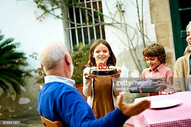 Children presenting cake and gift to grandfather