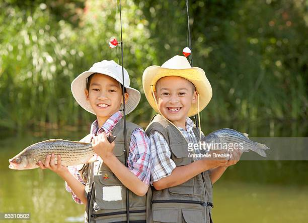 Children proudly show off their caught fish