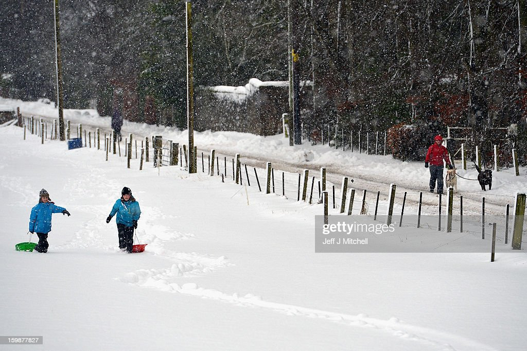 Children pull sledges through the snow in Blairgowrie on January 22, 2013 in Blairgowrie, United Kingdom.The Met Office has issued a red weather warning for parts of the Uk and advising against all non-essential travel as up to 30cm of snow is expected to fall in some areas today. The adverse weather has closed nearly 5,000 schools and caused many airports to cancel flights.