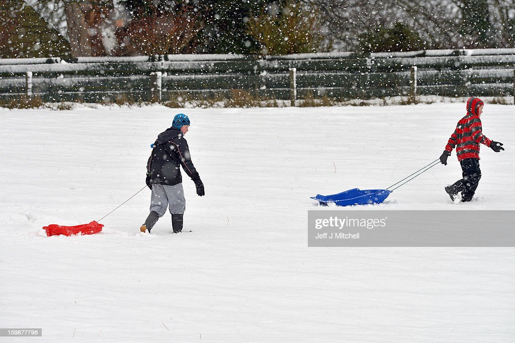 Children pull sledges through the snow in Coupar Angus on January 22, 2013 in Coupar Angus, United Kingdom.The Met Office has issued a red weather warning for parts of the Uk and advising against all non-essential travel as up to 30cm of snow is expected to fall in some areas today. The adverse weather has closed nearly 5,000 schools and caused many airports to cancel flights.