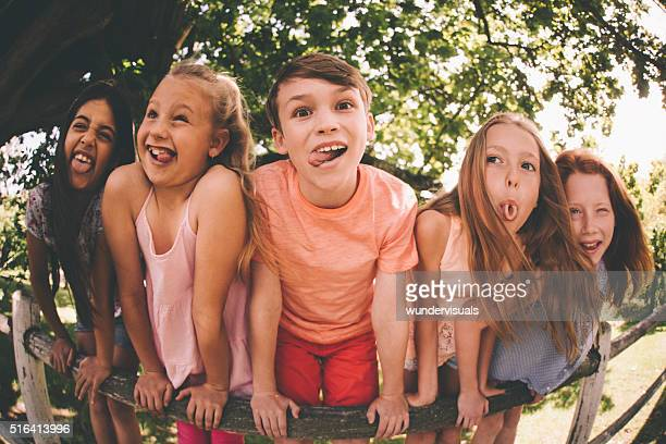 Children pulling silly faces at the camera in a park