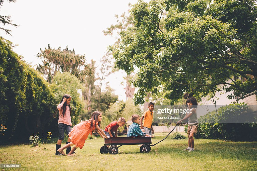 Children pushing and pulling friends in red wagon in park : Stock Photo