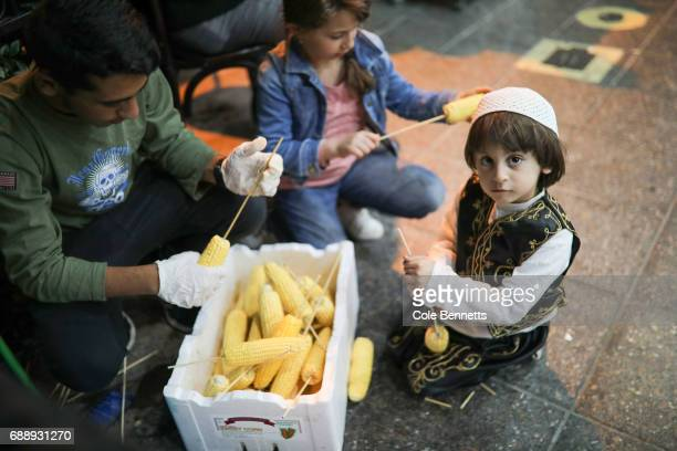 Children put sticks through cobs of corn during a street festival in the southwestern suburb of Lakemba on May 27 2017 in Sydney Australia Muslims...