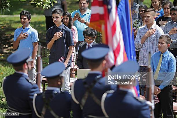 Children put their hands over their hearts during the singing of The StarSpangled Banner during a childrens citizenship ceremony at President...
