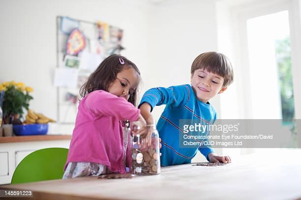 Children putting coins into jar
