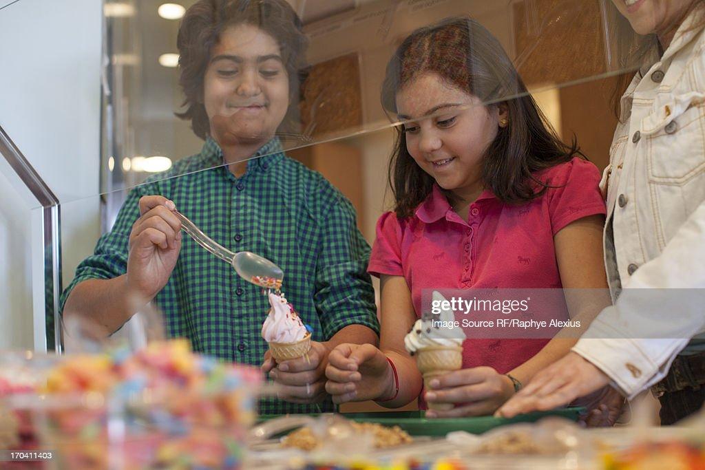 Children putting toppings on yogurt