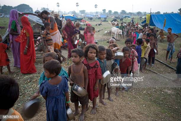 Children queue for a meal of khichri provided by a community kitchen in Gaushala camp for displaced people from Pirmuhammadpur village on the banks...