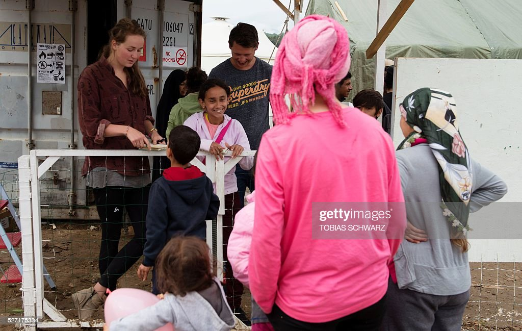 Children queue to enter a school at a makeshift camp for migrants and refugees at the Greek-Macedonian border near the village of Idomeni on May 2, 2016. Some 54,000 people, many of them fleeing the war in Syria, have been stranded on Greek territory since the closure of the migrant route through the Balkans in February. / AFP / TOBIAS