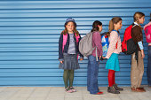 Children (8-11) queuing along wall, portrait of girl at end of queue