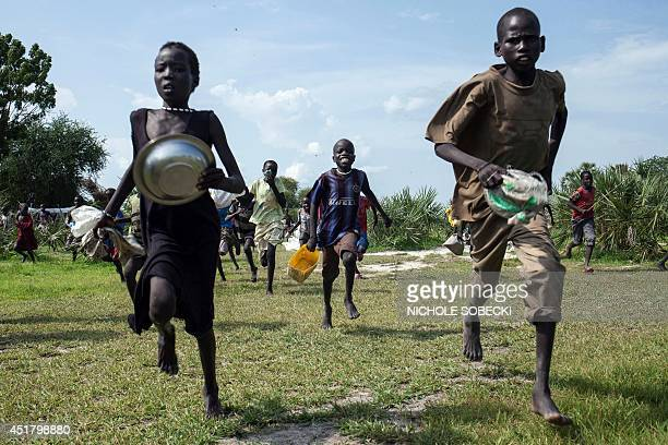 Children race into the drop zone to gather any food or seeds that were spilled during the air drop in Leer South Sudan on July 5 2014 Over 40 tons of...