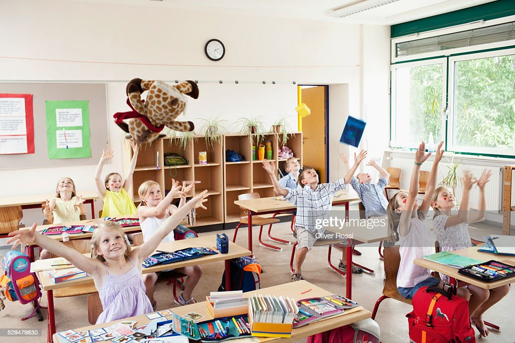 Children raising hands in classroom : Foto de stock