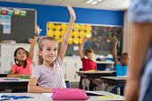Multiethnic group of young school children raising their hands to answer a question posed by the teacher. Group of elementary kids sitting in classroom and raising hands. Clever girl raising hand know