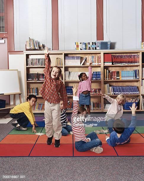 Children (5-7) raising hands up in library