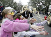 Children reach for mardi gras beads being thrown from a float during the Pontchartrain Mardi Gras parade February 18 2006 in the Garden District of...