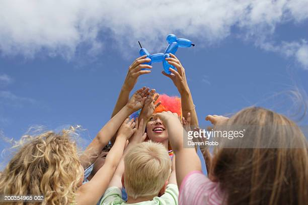 Children (6-7 years), reaching for balloon sculpture held by clown