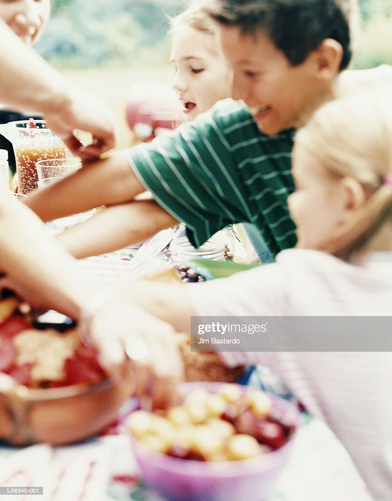 Children (5-10) reaching for food at picnic : Stock Photo