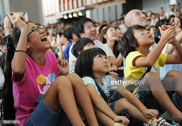 Children react to a projected live transmission image displaying the launch of Japan's new solidfuel Epsilon rocket carrying satellites from the...