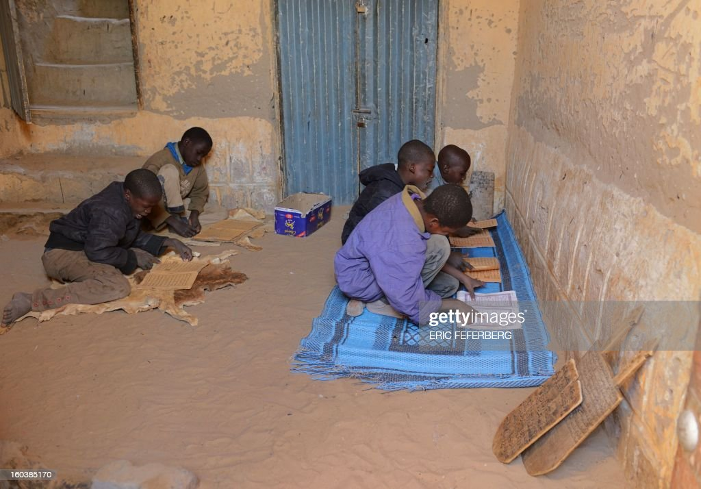 Children read from books of psalms as part of their religious studies with a marabout in Timbuktu, on January 30, 2013. French troops have taken up position today at the airport in Kidal, local sources said, the third major city in northern Mali after Gao and Timbuktu. AFP PHOTO / ERIC FEFERBERG