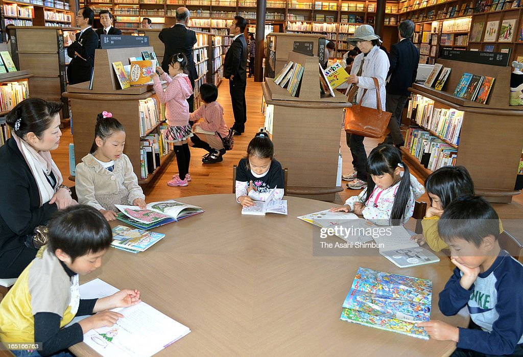 Children read picture books at reopened Takeo City Library on April 1, 2013 in Takeo, Saga, Japan. The city outsourses the library operation to Japan's video rental and bookstores chain Culture Convenience Club Co, that are know as the operator of 'Tsutaya', drawn attention for this new and unique attempt.