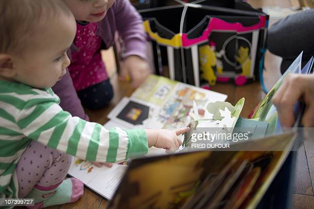 PELLEGRIN Children read popup books threedimensional or movable books on December 04 2010 in Paris Popup books made known in the 19th century by...