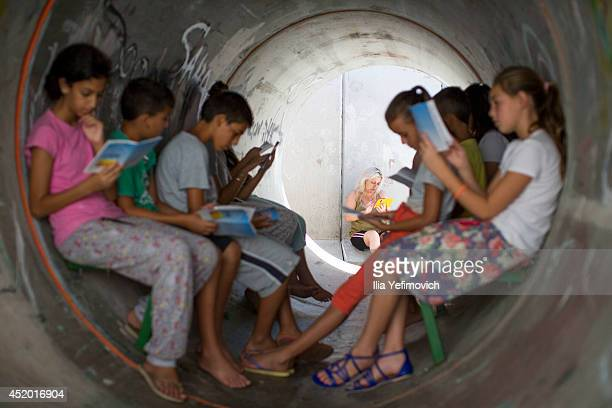 Children read while sitting in a street shelter in anticipation of Code Red sirens alerting of incoming rockets on July 11 2014 in Nitzan Israel The...