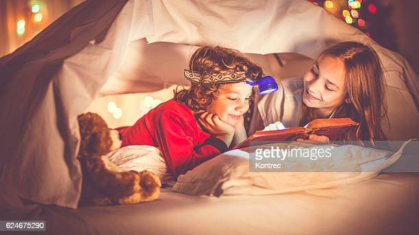 Children reading a book past their bedtime