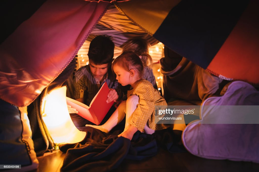 Children reading a story in blanket fort at night : Stock Photo