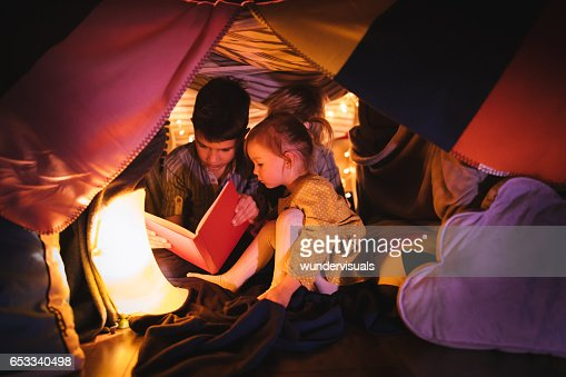 Children reading a story in blanket fort at night : Stock-Foto