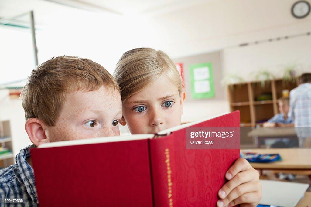 Children reading book in school : Stockfoto