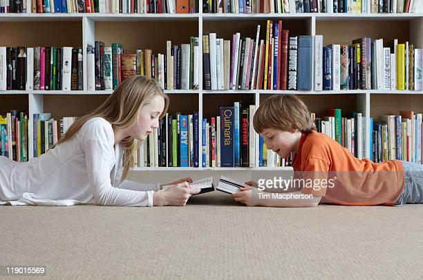 Children reading by bookshelves