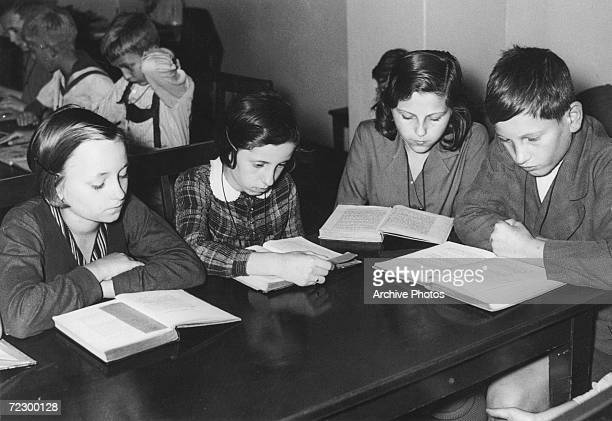Children reading in the library at their school in Alsace circa 1950
