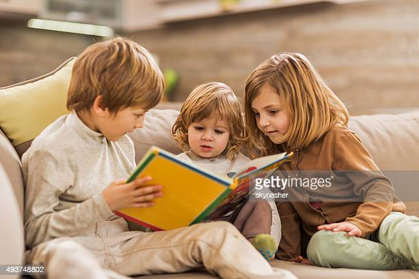 Children reading picture book at home.