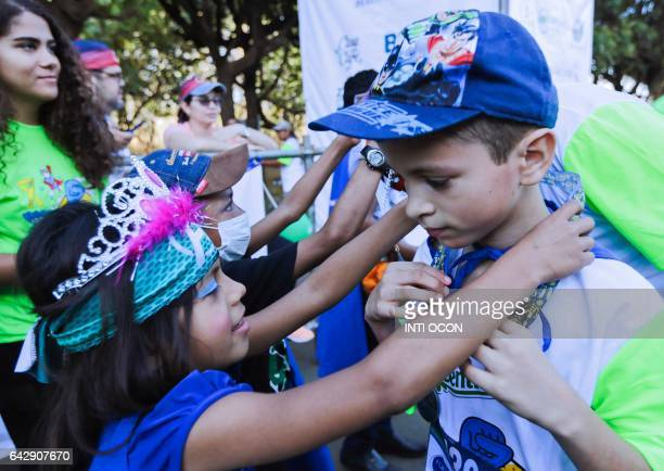 Children receive medals from children with cancer after completing the '5K Heroes with True Battles' walk in Managua on February 19 2017 People of...