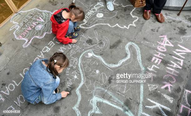 Children refugees from Crimea and from eastern Ukrainian regions draw symbolic maps depicting their regions and cities on the sidewalk at the...