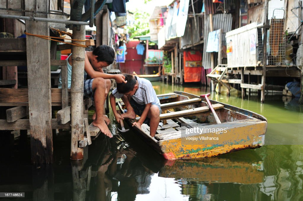 Children repair their boat before heading out to ferry passengers in Artex Compound in Malabon City on April 28, 2013 in Manila, Philippines. The residents of the former textile compound had to adjust their daily lives after flood waters submerged their low-lying village in 2004.